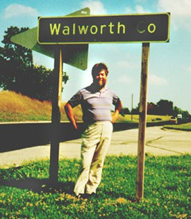 Ken Wilkinson stands by a sign for Walworth County, site of the first sociological study on community.