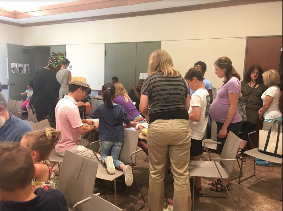 Families weaving bracelets together at Schlow Library in State College, PA