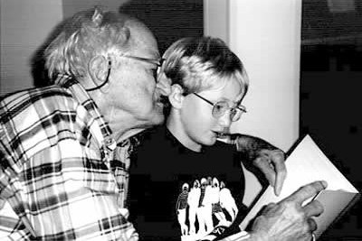 Charles Grossman (left), a resident at Foxdale Village, and Matthew Olivia, a student at the Friends School, share a quiet moment of reading together, State College, PA.  Photo: Mary Ann Curren, Director of Therapeutic Recreation, Foxdale Village.